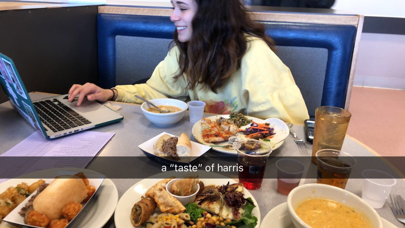 Dani Maney '21 sits at a booth in Harris with her laptop out and a number of plates piled with food from A Taste of Harris
