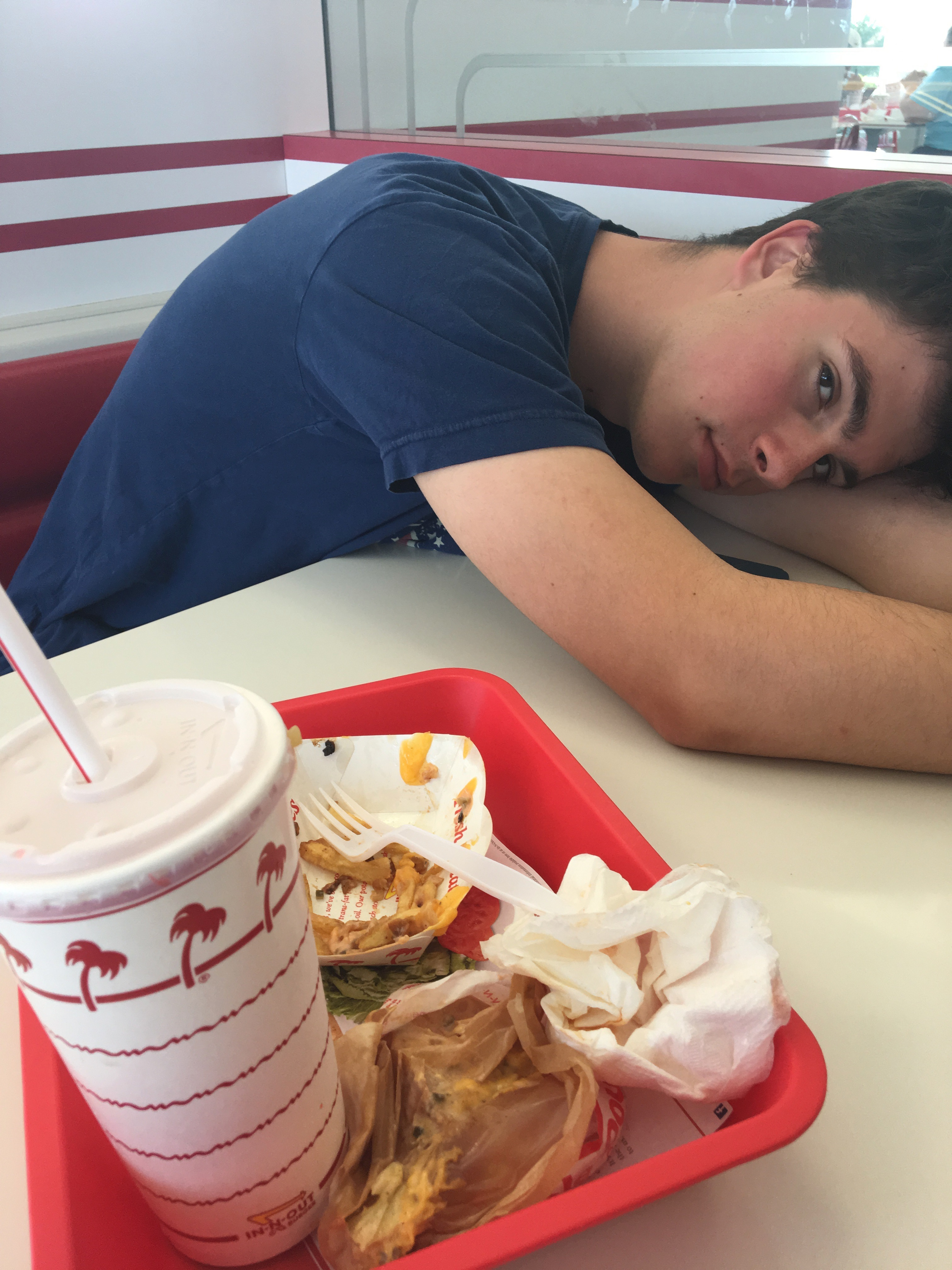Samuel rests his head on the table next to the remains of his lunch from In-N-Out Burger.