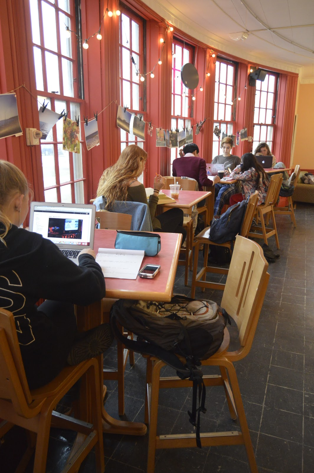 Students studying in front of the bright windows in the Coffee Closet