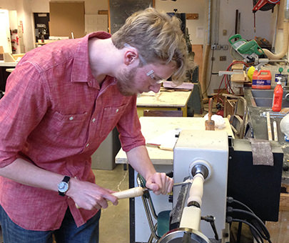 A student uses woodworking equipment in an art studio.
