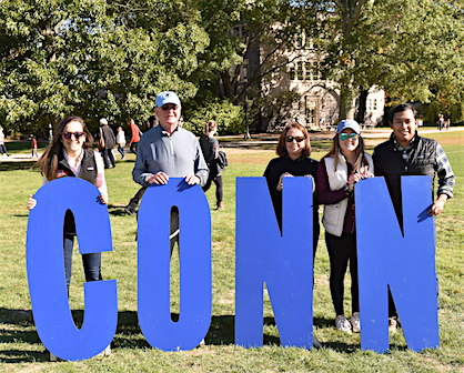 Parents pose with CONN letters at Fall Weekend