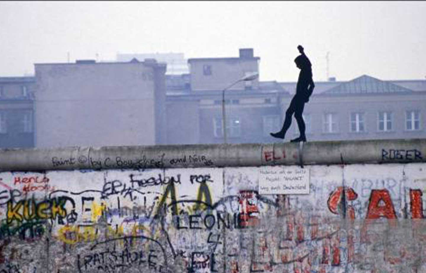 Image of man walking on the wall in Berlin in the early 1990s.