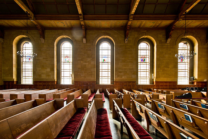 Harkness Chapel interior showing chestnut pews and stained glass windows