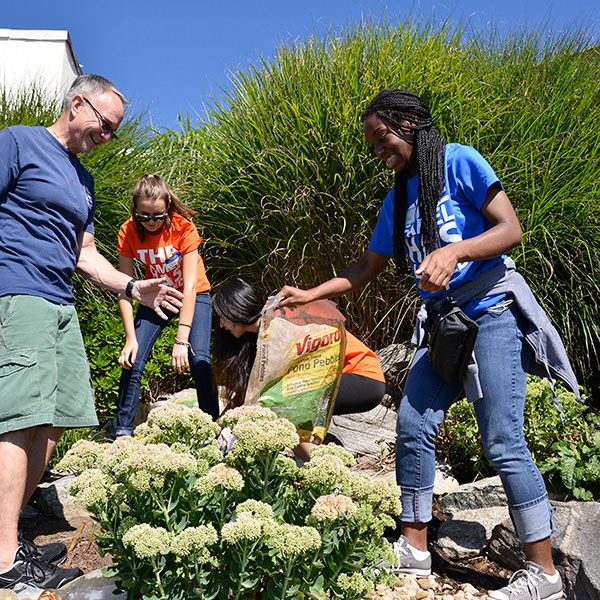 Student volunteers help clear planters at a local park.