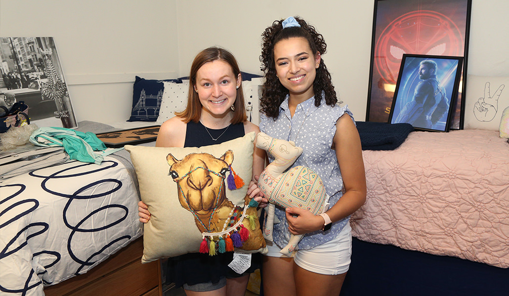 Two first-year students pose with their camel swag in their residence hall.
