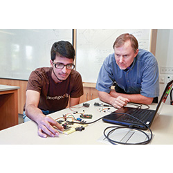 Robot research: Mohammed Khan '17, left, is working with Computer Science professor Gary Parker, right, on an independent research project to build a robot with the artificial intelligence to learn to drive without colliding with objects in its path.