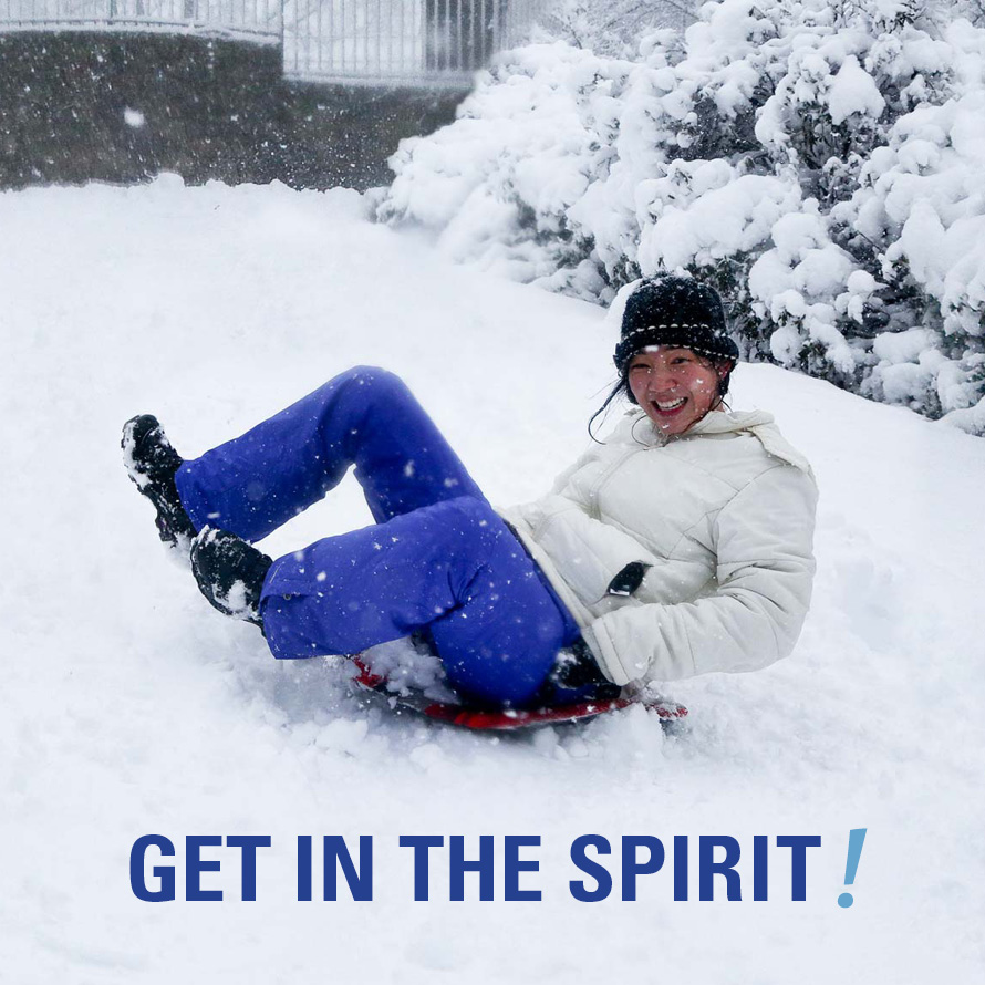 A student sledding in the Arboretum with the words 'Get in the Spirit!' below