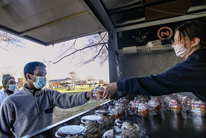 A student takes a cupcake from the NoRA cupcake truck.