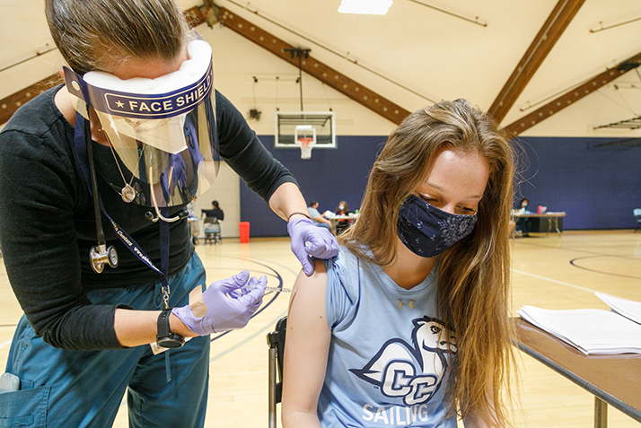 A nurse gives a student a COVID-19 vaccine.