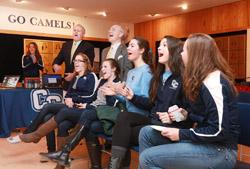 Members of the Connecticut College women's volleyball react as they watch the NCAA selection show with President Lee Higdon and Fran Shields, the Katherine Wenk Christoffers '45 Director of Athletics at Connecticut College.